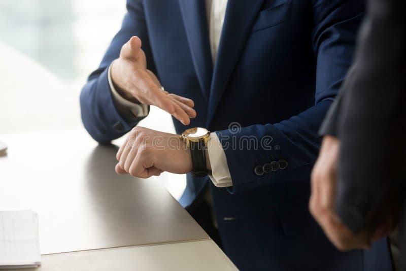 Homem de negócios que aponta no relógio de pulso, pontualidade, gestão de tempo fotografia de stock