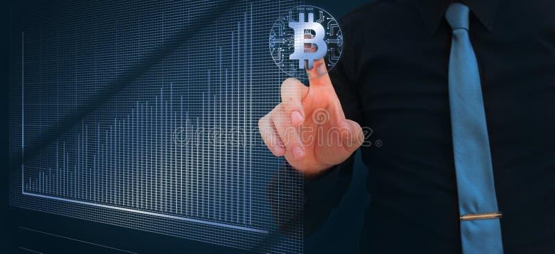 Homem de negócios que aponta o dedo no cryptocurrency digital do bitcoin com carta do mercado de valores de ação fotografia de stock