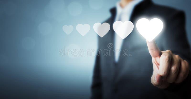 Homem de negócios que aponta o símbolo branco do coração à avaliação do aumento do fe fotografia de stock royalty free