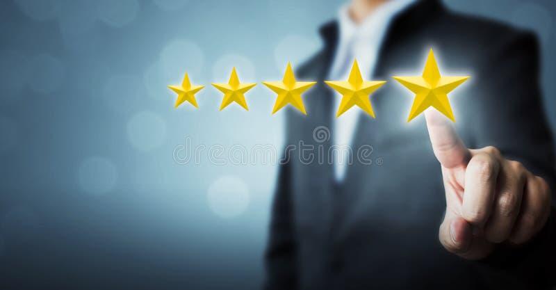 Homem de negócios que aponta um símbolo de cinco estrelas à avaliação do aumento dos comp(s) fotografia de stock royalty free