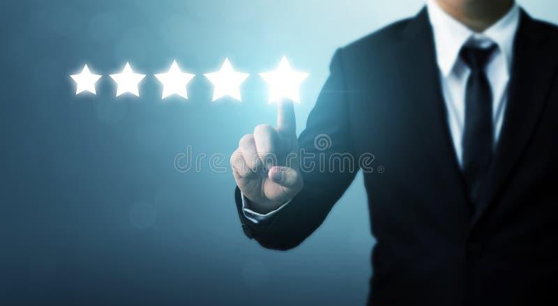 Homem de negócios que aponta um símbolo de cinco estrelas à avaliação do aumento dos comp(s) foto de stock