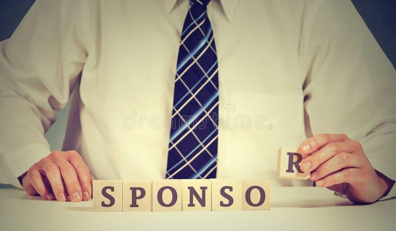Homem de negócios que arranja blocos de madeira na tabela Conceito da bolsa de estudos do patrocinador empresarial foto de stock royalty free
