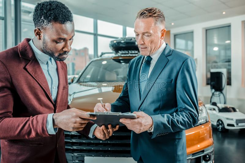 Homem de negócios que assina um contrato que compra um carro fotos de stock