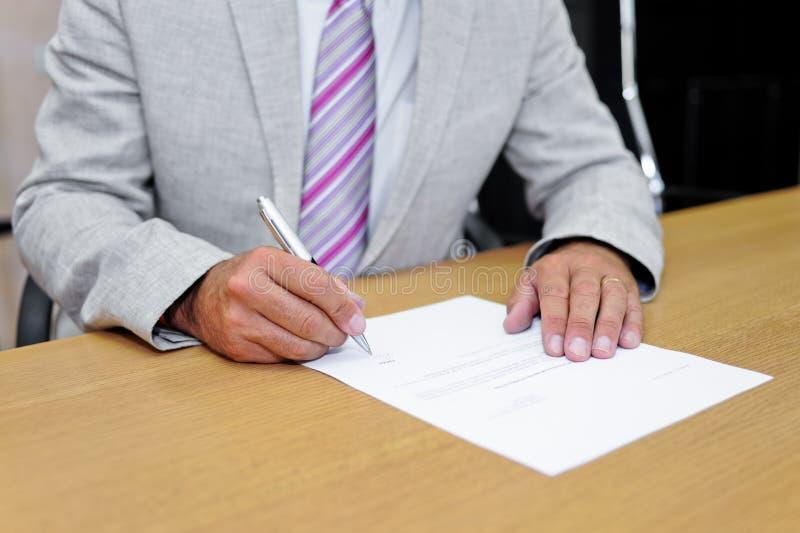 Homem de negócios que assina um formulário de papel imagem de stock
