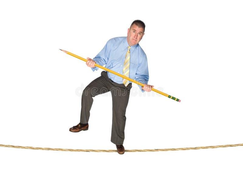 Homem de negócios que balança no tightrope foto de stock