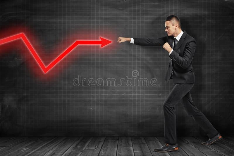 Homem de negócios que bate a seta vermelha do diagrama no fundo preto foto de stock royalty free