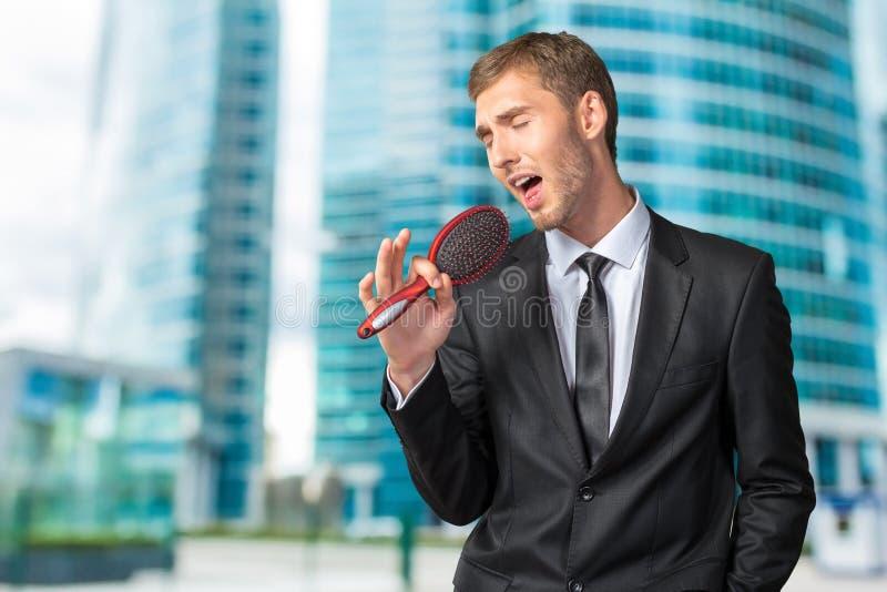Homem de negócios que canta como se no microfone imagem de stock