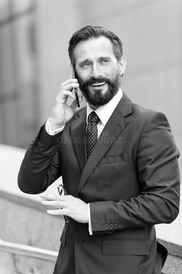 Homem de negócios que chama ativo com o cliente sobre o telefone celular fora do prédio de escritórios Gerente considerável na fa imagens de stock royalty free