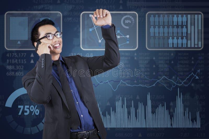 Homem de negócios que chama perto das estatísticas financeiras fotografia de stock royalty free