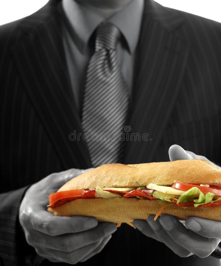 Homem de negócios que come o fast food da sucata fotos de stock royalty free