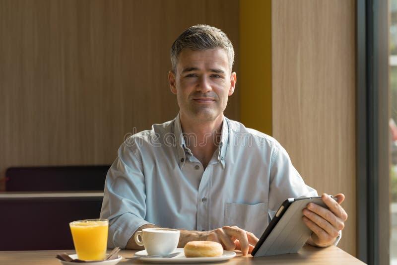 Homem de negócios que come o pequeno almoço imagens de stock royalty free