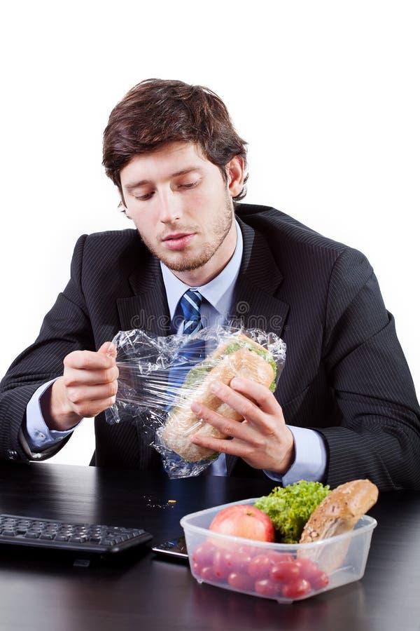 Homem de negócios que come o sanduíche imagens de stock royalty free