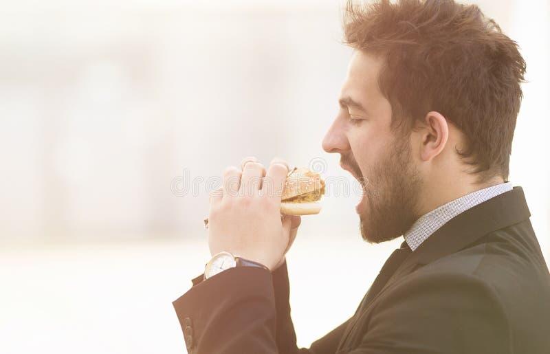 Homem de negócios que come sobre para ir fotografia de stock royalty free