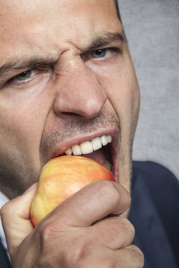 Homem de negócios que come uma maçã fotografia de stock royalty free