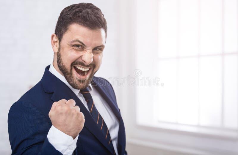 Homem de negócios que comemora a gritaria da vitória felizmente no escritório foto de stock