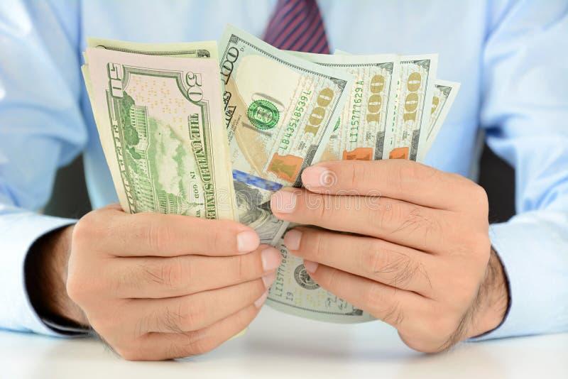 Homem de negócios que conta o dinheiro, contas do dólar americano (USD) imagem de stock