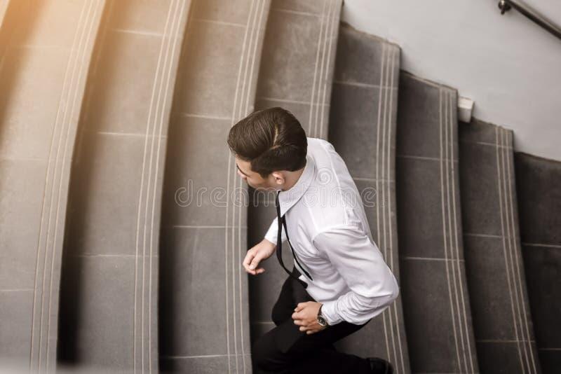 Homem de negócios que corre acima a escadaria que vai trabalhar fotografia de stock