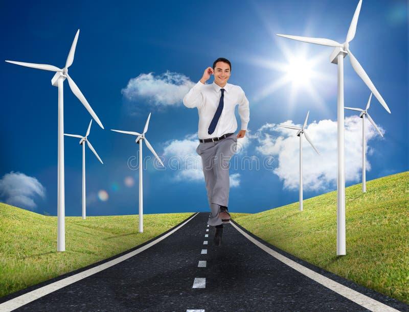 Homem de negócios que corre em uma estrada ao lado dos moinhos de vento imagens de stock