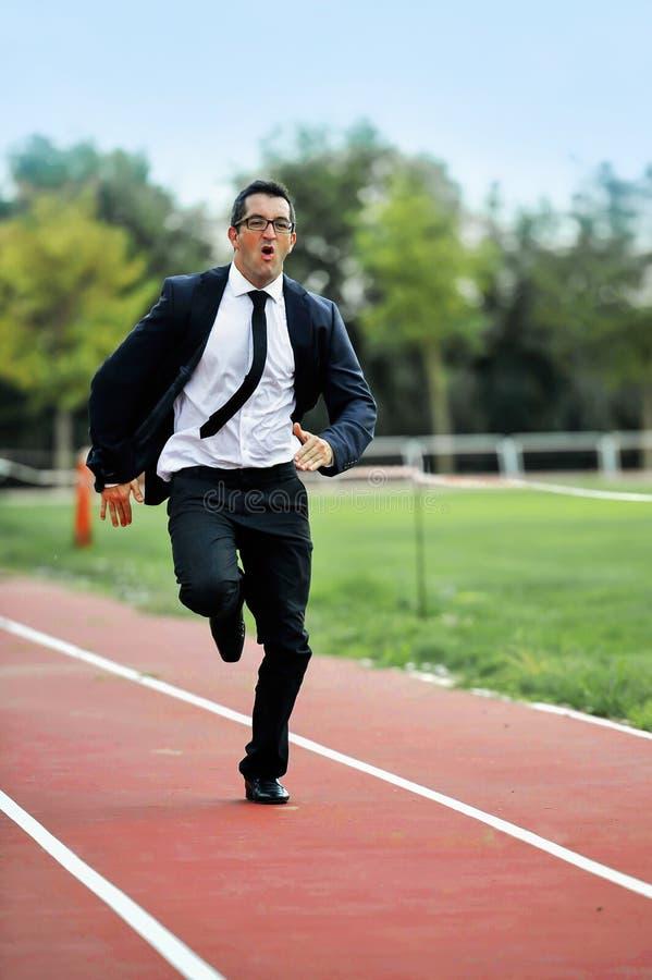 Homem de negócios que corre rapidamente na trilha atlética no esforço de trabalho e no conceito da urgência fotografia de stock royalty free