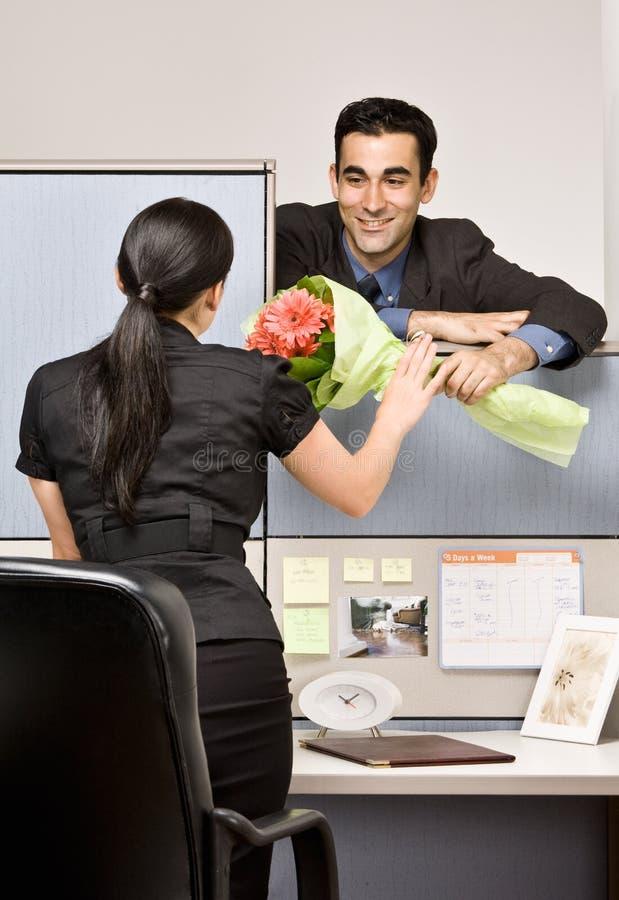 Homem de negócios que dá flores do colega de trabalho imagem de stock royalty free