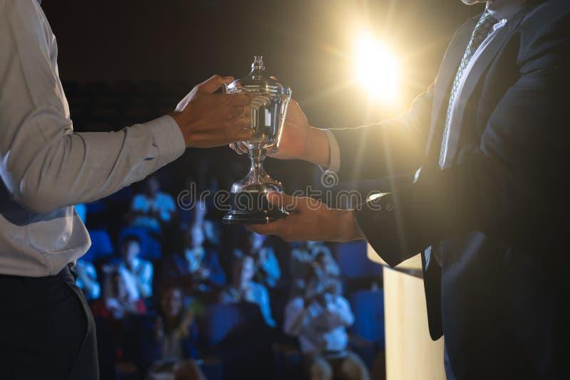 Homem de negócios que dá o troféu ao executivo masculino do negócio na fase no auditório imagem de stock royalty free