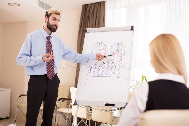 Homem de negócios que dá uma apresentação aos colegas que estão no flipchart com diagramas imagem de stock royalty free