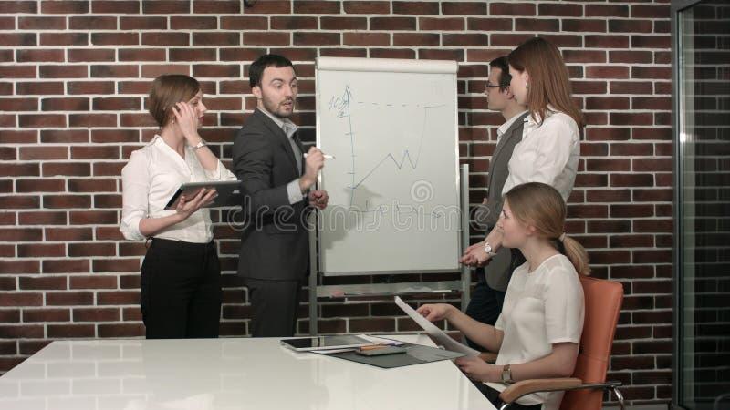Homem de negócios que dá uma apresentação no flipchart Conceito dos trabalhos de equipa imagens de stock