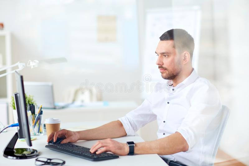 Homem de negócios que datilografa no teclado de computador no escritório fotografia de stock