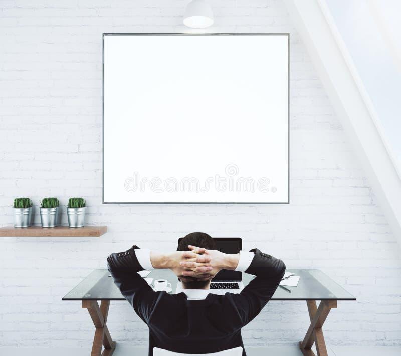 Homem de negócios que descansa em uma cadeira e que olha o pictur branco vazio fotos de stock