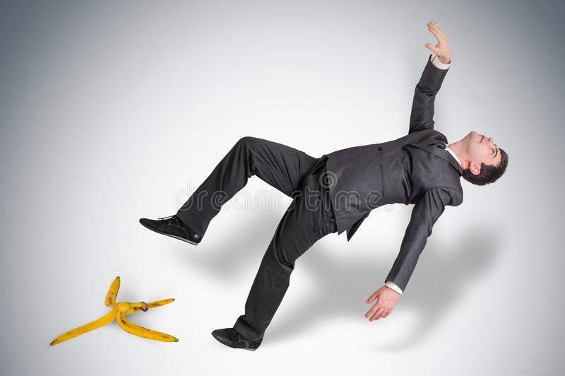 Homem de negócios que desliza e que cai de uma casca da banana imagem de stock