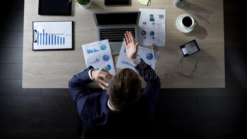 Homem de negócios que discute problemas financeiros sobre o smartphone, tristeza, vista superior fotos de stock royalty free