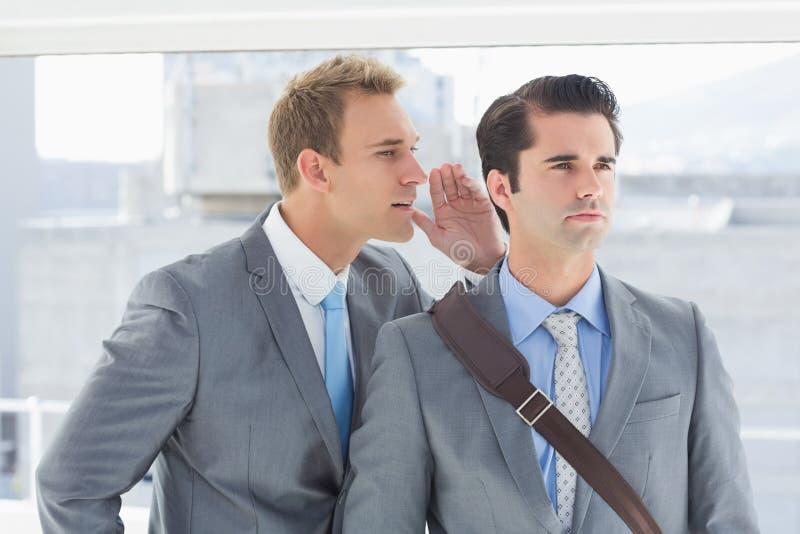 Homem de negócios que diz o segredo a seu colega imagem de stock