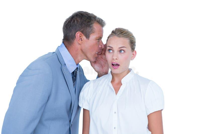 Homem de negócios que diz o segredo a uma mulher de negócios foto de stock