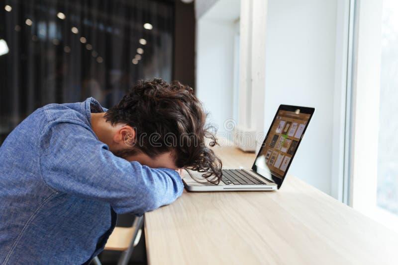 Homem de negócios que dorme na tabela com laptop imagens de stock royalty free