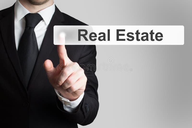 Homem de negócios que empurra bens imobiliários do botão liso foto de stock