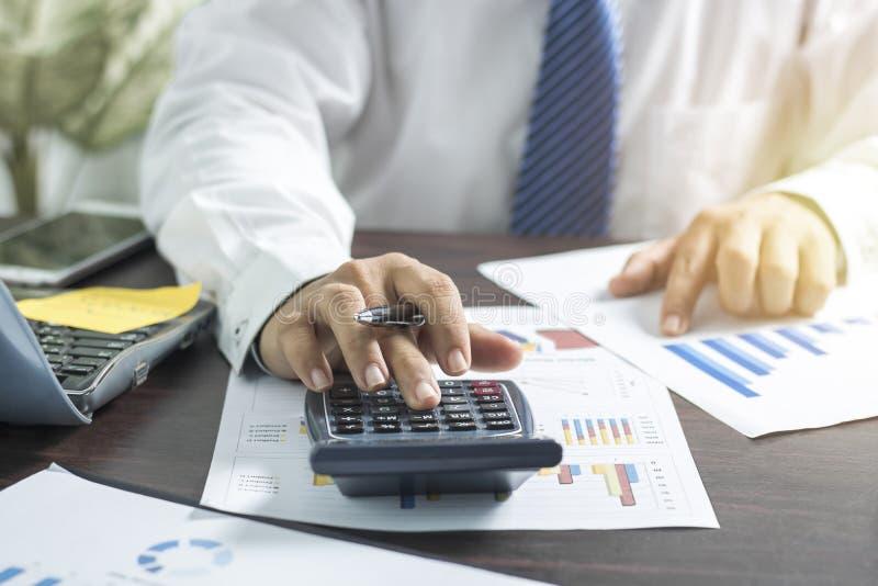 Homem de negócios que empurra e que pressiona na calculadora e que olha em bu imagens de stock royalty free