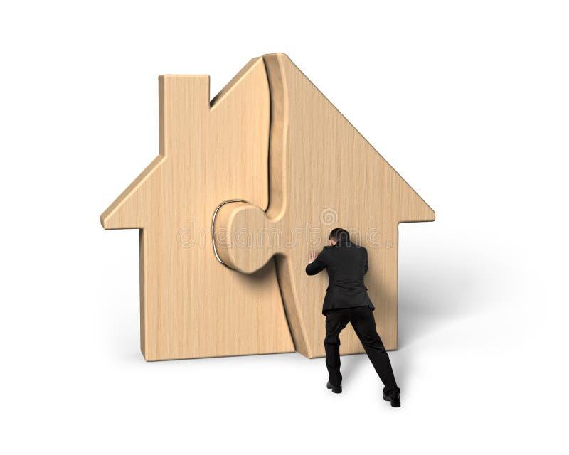 Homem de negócios que empurra enigmas de madeira de montagem da casa imagem de stock royalty free
