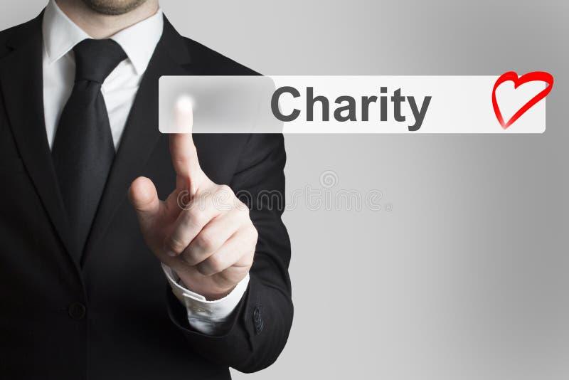 Homem de negócios que empurra o coração liso da caridade do botão fotografia de stock royalty free