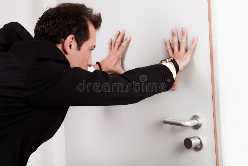 Homem de negócios que empurra a porta imagem de stock