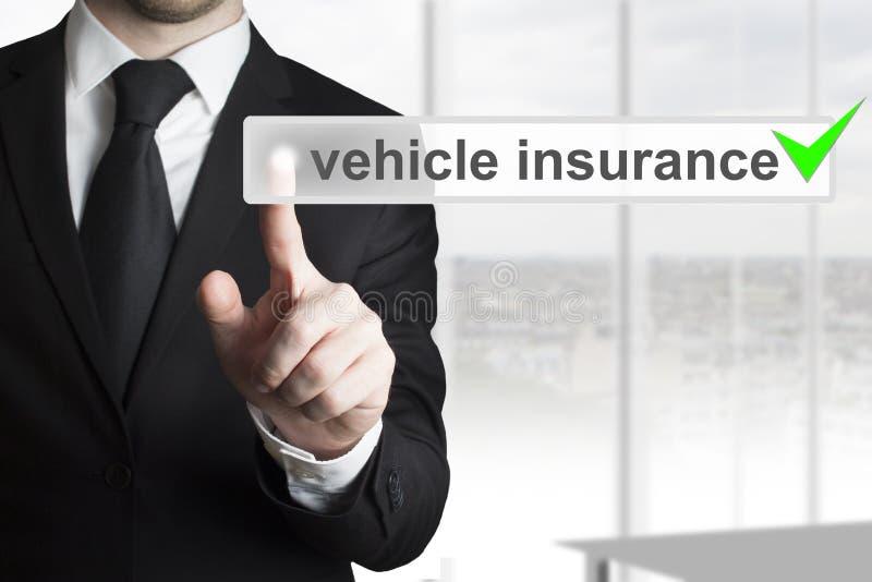 Homem de negócios que empurra a verificação do verde do seguro do veículo do botão foto de stock