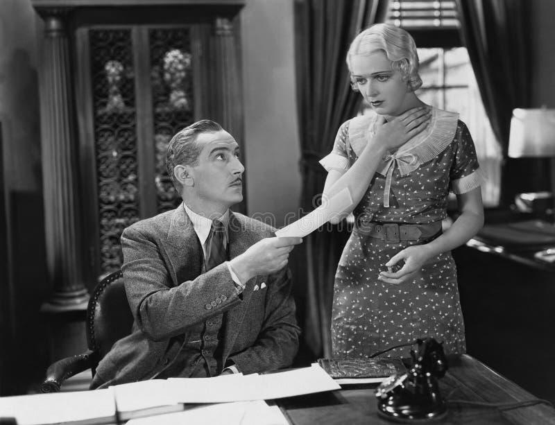 Homem de negócios que entrega o papel à mulher chocado (todas as pessoas descritas não são umas vivas mais longo e nenhuma propri foto de stock