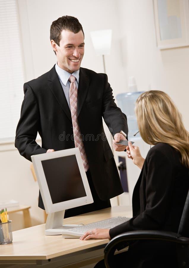 Homem de negócios que entrega a recepcionista seu cartão imagens de stock royalty free