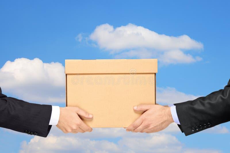 Homem de negócios que entrega um pacote a um isolat do homem imagem de stock royalty free