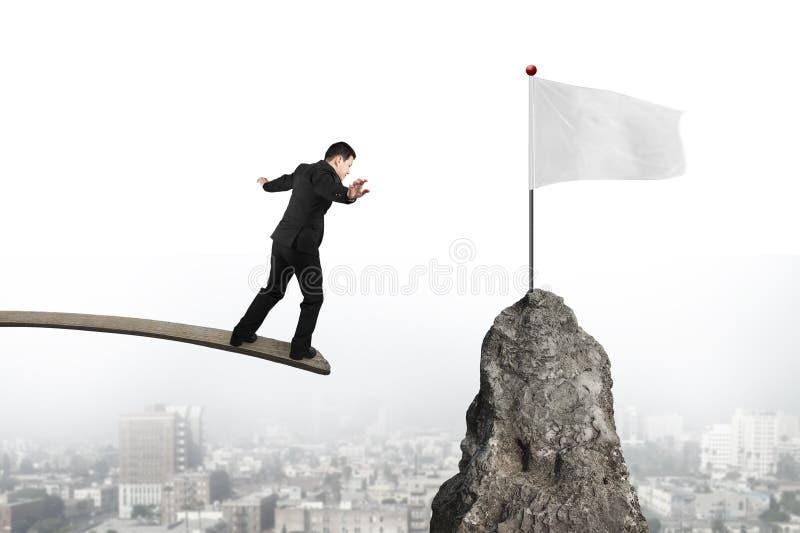 Homem de negócios que equilibra na placa de madeira com a bandeira branca vazia fotos de stock royalty free
