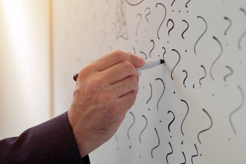 Homem de negócios que esboça muitos pontos de interrogação no whiteboard do escritório foto de stock