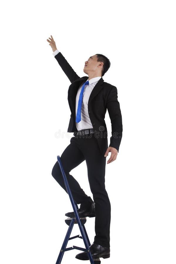 Homem de negócios que escala acima uma escada fotos de stock royalty free