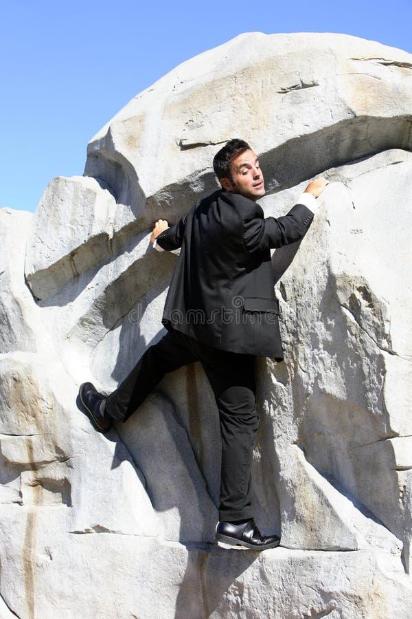 Homem de negócios que escala uma rocha imagens de stock