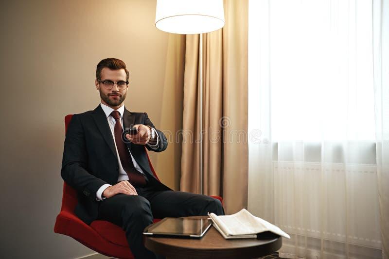Homem de negócios que escolhe o chanel na tevê na cadeira vermelha na sala de hotel fotografia de stock royalty free