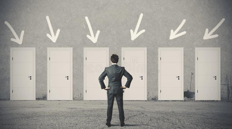 Homem de negócios que escolhe a porta direita fotos de stock