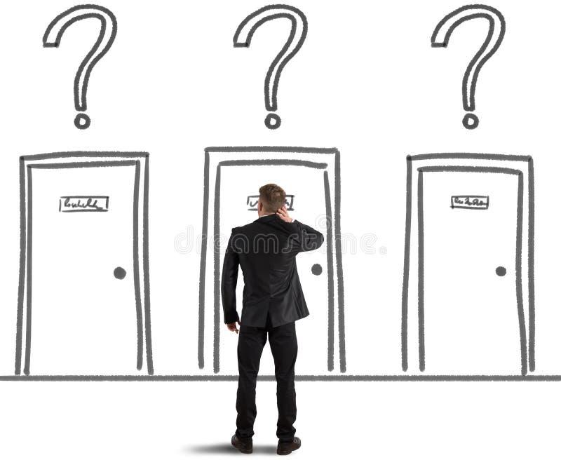 Homem de negócios que escolhe a porta direita imagem de stock